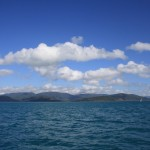 Blue sky, white clouds, green Whitsundays, blue ocean